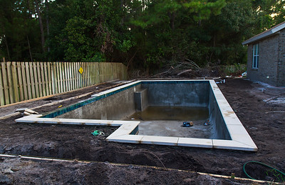 Coping installed, grounding wires attached, and forms set for enclosure footers