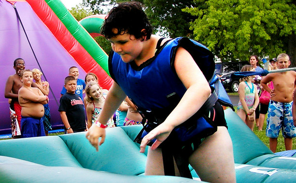 Debbie Blank | The Herald-Tribune<br /> Kayla Lawson, 10, Batesville, tests her strength at the football tug-of-war while other kids wait in line to perform the challenge.