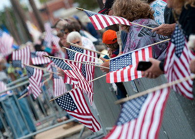 JAMIE MORTON/SPECIAL TO THE SUN HERALD November 10, 2012 Onlookers hold flags at the 12th Anniversary Gulf Coast Veterans Day Parade.