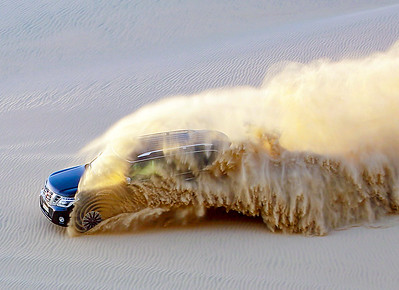 Car descending a Qatari sand dune