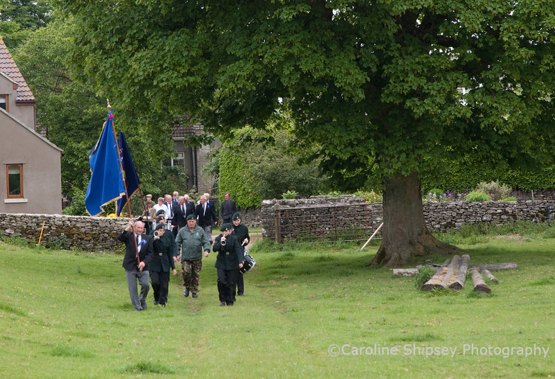 Fred Payne leads the Priddy Friendly Society across the field to church Priddy Friendly Society marching to church