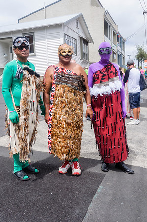 Three gentlemen wearing masks and traditional Maori feather cloaks, ready for the Pride Parade Ponsonby Auckland