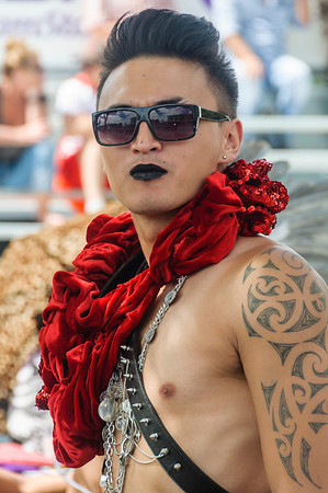 Young man participant with tattoo on his shoulder, wearing dark glass, a red ruffle, and a punk outfit, ready for the Pride Parade Ponsonby Auckland