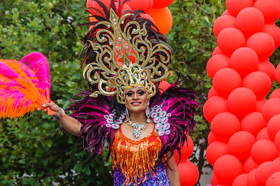 A participant in the Pride Parade in an elaborate and colourful costume, beside some red balloons Ponsonby Road Auckland
