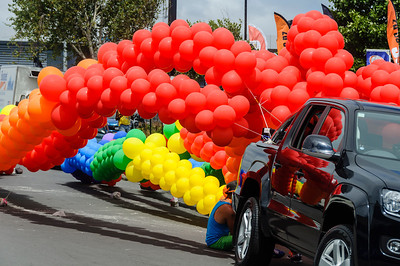 Streamers of red, yellow, green, and blue balloons tied to a car, before the Pride Parade Ponsonby Auckland