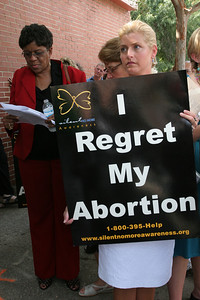 Jacquie Stalnaker of St. Paul Cathedral, Birmingham, Ala., was one of the riders aboard the Pro-Life Freedom Ride bus. Here she holds a sign during the Atlanta prayer service as a reminder of the abortion she once had.