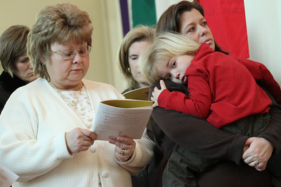 Debbie Gallo, left, and Julie Bugg, holding her four-year-old son Casey, stand for the commissioning of parish respect life leaders. Gallo and Bugg are members of Prince of Peace Church, Flowery Branch.