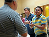 Fr. Thi Pham shares a laugh, and snack, with Fr. Rick DiLeo.  John Kuxhause, province accountant, is in the background.