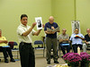 Dn. Mark Mastin holds Fr. Tom Garvey's photo during a brief ceremony to remember those who died during the past six years.