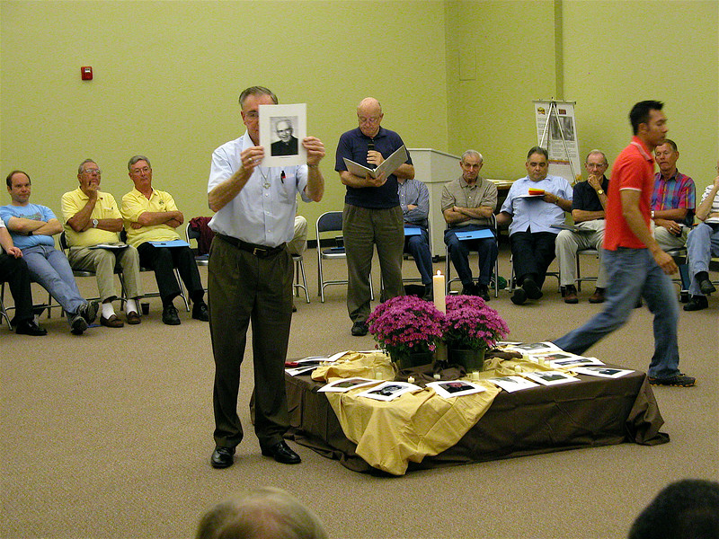 Br. Ben Humpfer displays a photo of Fr. Tom Simcox during the remembrance ceremony.