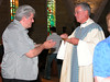 Fr. Chuck Wonch receives communion from Fr. Tom.
