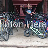 RAGBRAI XL Hospitality Committee member Cathy Crosser stands with dozens of used bicycles which will be used in the Clinton welcoming display. • Submitted photo