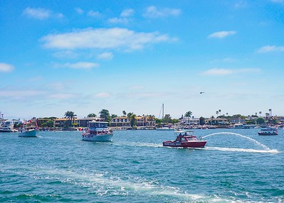 Led by the OC Sheriff patrol boat, the parade cruises  Newport Beach Harbor on a perfect day!
