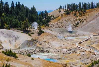 Bumpass Hell is a collection of steaming 200-300 degree gurgling hot pools. A lone photographer captures the scene.