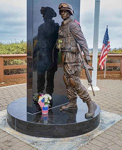 Flags and Flowers adorn the sculpture honoring the 1st Marine Batallion