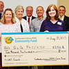 Debbie Blank | The Herald-Tribune<br /> Melody Belcher (holding check at right), Safe Passage nonresidential services director, received $2,500 for materials and supplies from (from left) trustee Jerry Lamb, general manager Keith Mathews, trustees Carla Elston, Judy Copeland, Keith Allhands, Steve Black and Owen Menchhofer and office manager Barry Lauber.