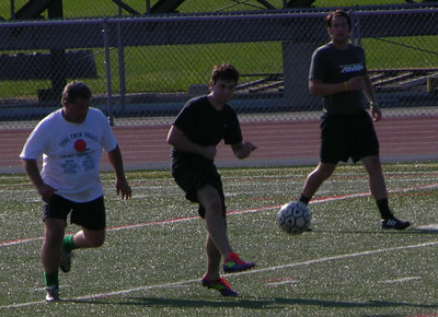 A player lobs a pass to assist on a goal during the alumni soccer match at Raiderfest 2013 at Twin Valley High School Aug. 24.