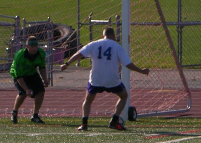 A striker challenges the keeper during the alumni soccer game at Raiderfest 2013.