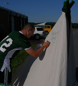 A Twin Valley football player signs the teepee at Raiderfest 2013 at Twin Valley High School Aug. 24.