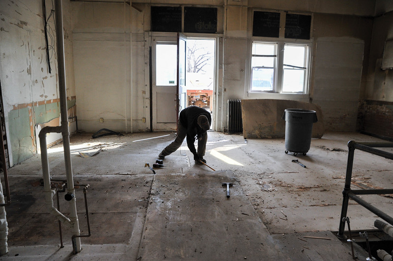 Ashleigh Fox | The Sheridan Press<br /> A member of the O'Dell construction crew rips up boards covering part of the floor in the railroad station building on Broadway Street in Sheridan Thursday, March 15, 2018. Crews started gutting the building this month and plan to restore it back to its original charm.
