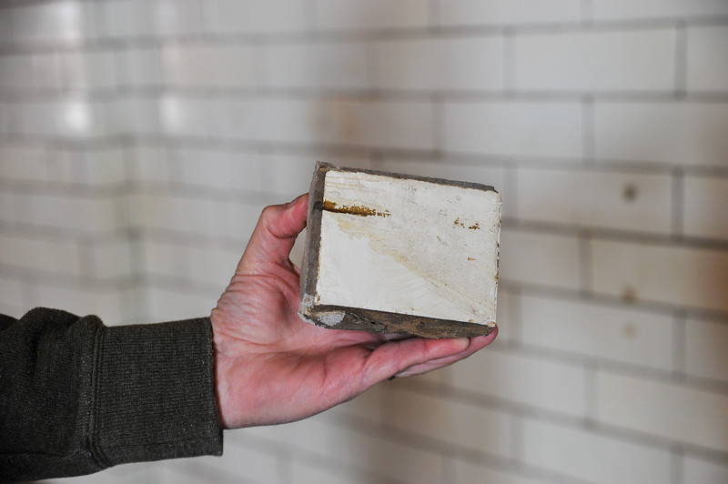 Ashleigh Fox | The Sheridan Press<br /> Dan Stalker holds a part of the glazed brick taken from the original wall in the railroad station Thursday, March 15, 2018. The Tiffany brick originated from Chicago.