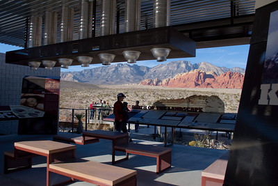 Photograph at Red Rock Canyon Visitor Center in Red Rock Canyon Park Nevada is the focal point for visitor orientation.  Red Rock Canyon Visitor Center offers information and interpretation about recreation opportunities, wildlife, vegetation, geology, cultural resources. Red Rock Canyon Visitor Center covers 2 acres and has a large indoor exhibit area which is funded and has been created by RRCIA. The displays depict the cultural and natural resources of the Conservation area. Located within the visitor center is also a bookstore and gift store. RRCIA is a non-profit organization that researches and offers interpretive information about assisting with BLM educational endeavors. In addition to the exhibit a book and gift store have displays of unique items, such as those created by local artisans, jewelry, books, and maps.
