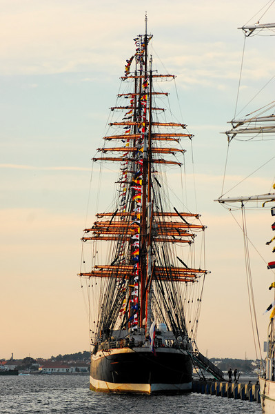 "Sedov<br /> The four masted sail training barque of the University of Murmansk, Sedov, is the vessel on which the young cadets of the university train to become officers, mechanics and radio specialists.<br /> Sedov can accommodate up to 320 people on board among which 75 are crew members, 100 to 120 cadets and in some years, as many as 45 trainees of any nationality to discover life aboard a tall ship. This training takes place during a journey of 3 to 4 months along European coasts and will take advantage of cultural and economic exchanges with the ports.<br /> Launched in Kiel in 1921 at the shipbuilding yard Krupp, Sedov (then named Magdalene Vinnen) with an auxiliary diesel engine with some 128hp, was exclusively dedicated to the transport of goods and the crew were already partially made up of cadets.<br /> In 1936, Magdalene Vinnen was sold to Norddeutscher Lloyd, Bremen and was renamed Kommodore Johnsen. She carried out numerous circumnavigations, transporting some wheat, some coal and some cereals.<br /> The Second World War put an end to these journeys as an ocean-going vessel, but she continued to train cadets in the Baltic where her journeys lasted from 5 to 6 weeks. During this time of scarcity of fuel, she would sail only. She came under Russian state ownership after the surrender of Germany.<br /> The four masted barque was then renamed ""Sedov"" after the polar explorer Georgij Sedov who died during an investigation in the Arctic in 1914. Sedov navigated as an oceanographical vessel until 1966, she was then put in reserve to Kronstadt and she reappeared in the 1970's.<br /> Between the 1970's and 1981 various works were carried out which cost in the region of 1 million roubles. She left the shipyard in 1981 and, with Riga as the port of registry, she embarked henceforth cadets from schools of navigation of Kalingrad and Murmansk.<br /> The fall of the Wall in 1989 and the Proclamation of Independence of Latvia in 1991 influenced the fate of Sedov. Living in the lap of Russia, she left Riga for Murmansk, her new port of registry, and fell henceforth to the school of the navy of the city which assured her management and maintenance."