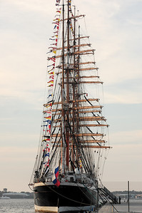 """Sedov [Russia] The four masted sail training barque of the University of Murmansk, Sedov, is the vessel on which the young cadets of the university train to become officers, mechanics and radio specialists. Sedov can accommodate up to 320 people on board among which 75 are crew members, 100 to 120 cadets and in some years, as many as 45 trainees of any nationality to discover life aboard a tall ship. This training takes place during a journey of 3 to 4 months along European coasts and will take advantage of cultural and economic exchanges with the ports. Launched in Kiel in 1921 at the shipbuilding yard Krupp, Sedov (then named Magdalene Vinnen) with an auxiliary diesel engine with some 128hp, was exclusively dedicated to the transport of goods and the crew were already partially made up of cadets. In 1936, Magdalene Vinnen was sold to Norddeutscher Lloyd, Bremen and was renamed Kommodore Johnsen. She carried out numerous circumnavigations, transporting some wheat, some coal and some cereals. The Second World War put an end to these journeys as an ocean-going vessel, but she continued to train cadets in the Baltic where her journeys lasted from 5 to 6 weeks. During this time of scarcity of fuel, she would sail only. She came under Russian state ownership after the surrender of Germany. The four masted barque was then renamed """"Sedov"""" after the polar explorer Georgij Sedov who died during an investigation in the Arctic in 1914. Sedov navigated as an oceanographical vessel until 1966, she was then put in reserve to Kronstadt and she reappeared in the 1970's. Between the 1970's and 1981 various works were carried out which cost in the region of 1 million roubles. She left the shipyard in 1981 and, with Riga as the port of registry, she embarked henceforth cadets from schools of navigation of Kalingrad and Murmansk. The fall of the Wall in 1989 and the Proclamation of Independence of Latvia in 1991 influenced the fate of Sedov. Living in the lap of Russia, she left Riga """