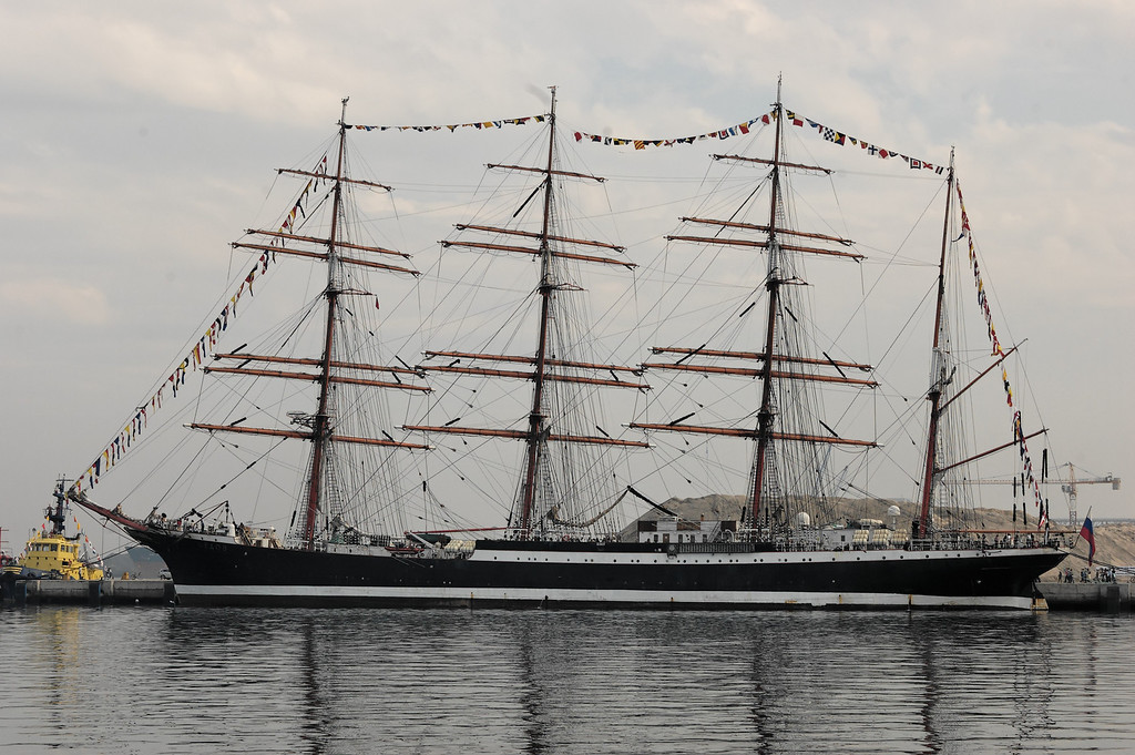 """Sedov<br /> The four masted sail training barque of the University of Murmansk, Sedov, is the vessel on which the young cadets of the university train to become officers, mechanics and radio specialists.<br /> Sedov can accommodate up to 320 people on board among which 75 are crew members, 100 to 120 cadets and in some years, as many as 45 trainees of any nationality to discover life aboard a tall ship. This training takes place during a journey of 3 to 4 months along European coasts and will take advantage of cultural and economic exchanges with the ports.<br /> Launched in Kiel in 1921 at the shipbuilding yard Krupp, Sedov (then named Magdalene Vinnen) with an auxiliary diesel engine with some 128hp, was exclusively dedicated to the transport of goods and the crew were already partially made up of cadets.<br /> In 1936, Magdalene Vinnen was sold to Norddeutscher Lloyd, Bremen and was renamed Kommodore Johnsen. She carried out numerous circumnavigations, transporting some wheat, some coal and some cereals.<br /> The Second World War put an end to these journeys as an ocean-going vessel, but she continued to train cadets in the Baltic where her journeys lasted from 5 to 6 weeks. During this time of scarcity of fuel, she would sail only. She came under Russian state ownership after the surrender of Germany.<br /> The four masted barque was then renamed """"Sedov"""" after the polar explorer Georgij Sedov who died during an investigation in the Arctic in 1914. Sedov navigated as an oceanographical vessel until 1966, she was then put in reserve to Kronstadt and she reappeared in the 1970's.<br /> Between the 1970's and 1981 various works were carried out which cost in the region of 1 million roubles. She left the shipyard in 1981 and, with Riga as the port of registry, she embarked henceforth cadets from schools of navigation of Kalingrad and Murmansk.<br /> The fall of the Wall in 1989 and the Proclamation of Independence of Latvia in 1991 influenced the fate of Sedov. Livi"""