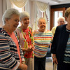 From left, Marilyn McDermott Clements, Joan Schneder Crable, Mary Theresa Oaks Shea and Ann Burwinkel Murray listen to former classmate speak at a reunion of the 1950 Regina High School class June 3 at Salem Heights.