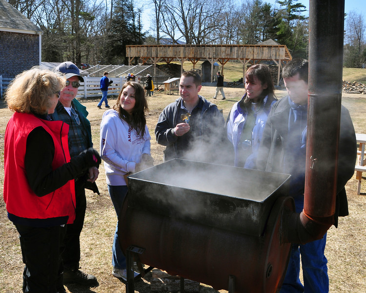 "Educator Kathy Johnson, of The Remick Farm, explains to (l to r) Guy Mailhot, of Stratford Hollow, NH, Rachael & Mark Mailhot, Ginette & Bob Fosher, all of Groveton, NH,  how the ""backyard boiler"" is used to reduce sap, gathered from maple trees, down to a maple syrup, during the annual maple sugaring event, which was held at The Remick Country Doctor Museum and Farm, in Tamworth, NH, on March 27th, 2010."