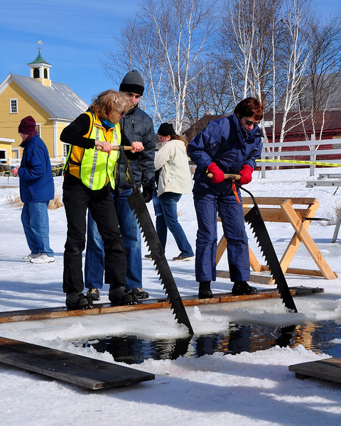 Kathy Johnson, of The Remick Country Doctor Museum and Farm, in Tamworth, NH, shows Shimon Rura, of Somerville, MA, and Marlene Cloutier, of Colebrook, NH, how to properly saw pond ice into blocks, for harvesting & storage in the farm's ice house. This activity was part of the annual Ice Harvesting and Winter Carnival event, on Saturday, February 13, 2010.