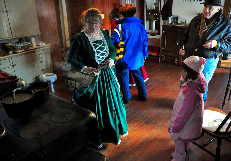 Susan Junkins, of The Remick Country Doctor Museum & Farm, shows 6 year old Suzanne Reynolds, of Chelmsford, MA, how to pop corn on the wood fired cookstove, during The Museum's Victorian Christmas event, which was held Saturday, December 12th, 2009, in Tamworth, NH.
