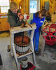 Kathleen Johnson, of the Remick Country Doctor Museum & Farm, in Tamworth NH, demonstrates traditional apple cider making with the apple press, as Museum Educator looks on. This demonstration was part of the Farm's Traditional Thanksgiving event, held on November 14th, 2009