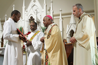 Archbishop Wilton D. Gregory, second from right conducts the opening prayer as Morehouse College senior Anthony McCool holds the book and Deacons William Simmons III, left, and Bill Monahan standby on the altar.