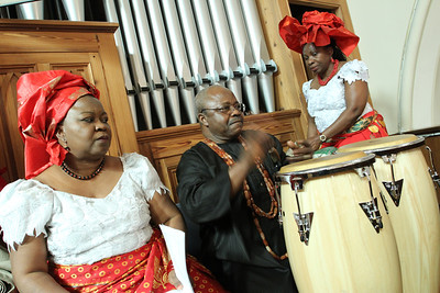 Dr. Infeyani Anikpe, center, of St. Paul of the Cross Church, Atlanta, and Uche Chioke, right, of St. Thomas the Apostle Church, Smyrna, conduct the drum call during the Call to Worship. Looking on is Ada Ngoddy of St. Matthew Church, Tyrone.
