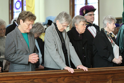 (Front row, l-r) Dominican Sisters Emeric Bauch, Patricia Caraher, Marie Sullivan and Sister of Saint Joseph Louise Sommer stand as Archbishop Wilton Gregory, the main celebrant, leads a prayer before the congregation. Women religious and priests were honored during the Jan. 19 Mass.