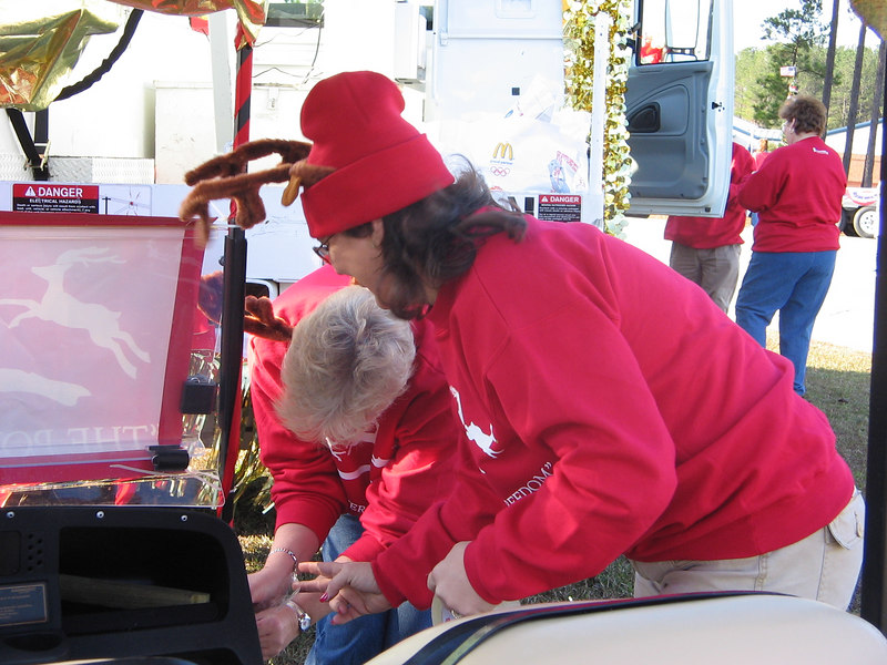 """Michelle and Gloria work on Whit's """"Golden Golfcart""""."""