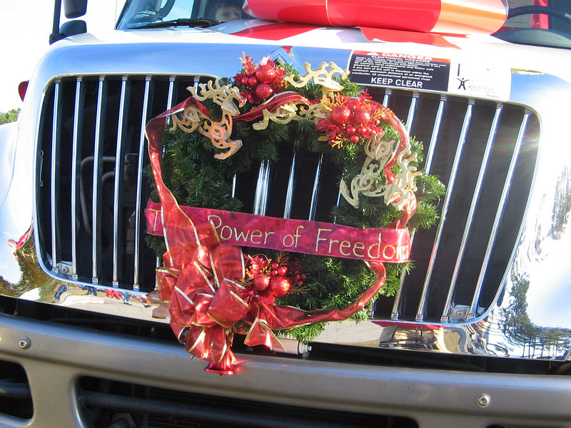 The wreath was a team effort. Kim bought the reindeer. Anne spray-painted them gold. Becky wrote the banner ribbon and made the bow. She and Gloria arranged it. Then Melvin and Sam, Michelle's husband, got the wreath on the truck.