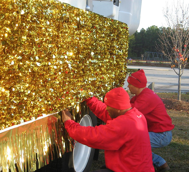 Melvin and Doug work to get one side of the bucket truck covered with a sheet of gold foil.