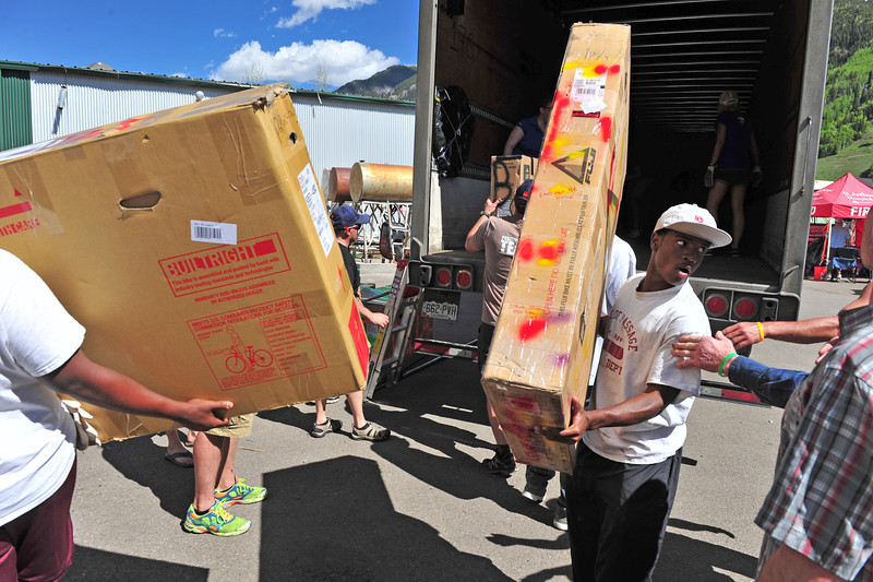 Young men from Rite of Passage unload boxed bikes in Telluride with speed and skill. The organization handled luggage for riders throughout the week-long event.