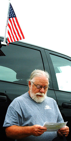 "Debbie Blank | The Herald-Tribune<br /> Participant Rusty Pike, Charlestown, read a prayer near a flag-adorned vehicle: ""May we pledge ... this same service and devotion"" as the soldiers and Marines who recently died."