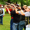 Debbie Blank | The Herald-Tribune<br /> As rain began to mist, volunteers began a 21-gun salute in Liberty Park.