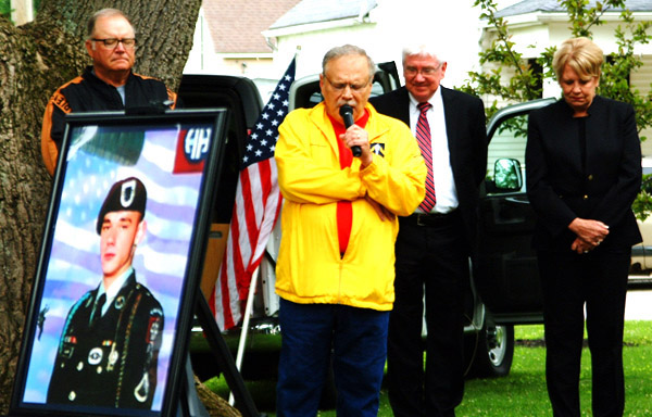 "Debbie Blank | The Herald-Tribune<br /> With a photo of Chad Keith in the foreground, the Rev. Dave Johnston presented a prayer. He was hopeful the Ride to Remember would be ""a powerful and affirmative experience ... (about) the spirit of liberty."" He asked God to watch over Gold Star families ""who have experienced sadness and the difficulties of war."" Surrounding him are (from left) state Rep. Randy Lyness, Batesville Mayor Mike Bettice and state Rep. Cindy Ziemke."