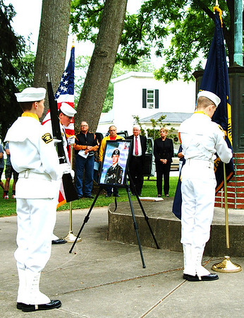 Debbie Blank | The Herald-Tribune<br /> As U.S. Naval Sea Cadet Corps Flying Tigers Squadron members present two flags to open the ceremony at Liberty Park, one glances at a photo of Chad Keith, who was just a big older than them when he was killed in action.