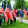 Debbie Blank | The Herald-Tribune<br /> Indiana Patriot Guard Southeast Indiana Region members and other volunteers held flags at the start of the first Ride to Remember service in Liberty Park. Batesville High School graduate Sgt. Chad Keith, 21, died July 7, 2003, in Baghdad, Iraq, during Operation Iraqi Freedom. The park contains a tree and rock in his memory. He is buried at Arlington National Cemetery. There were 13 stops on the 300-mile June 8-9 caravan to honor 16 fallen Marines and soldiers.