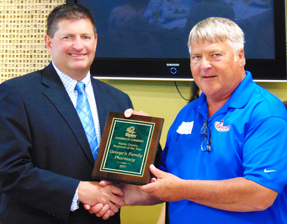"Debbie Blank | The Herald-Tribune<br /> George's Pharmacy founder George Gillman (right) accepted the Business of the Year plaque from chamber President Phillip Hart by observing, ""Without our great employees, we would not have the stores we have."""