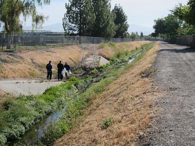 Volunteers collecting trash along the creek.