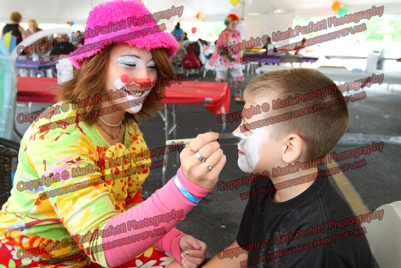 Bibbles the clown paints the face of John Dutcher