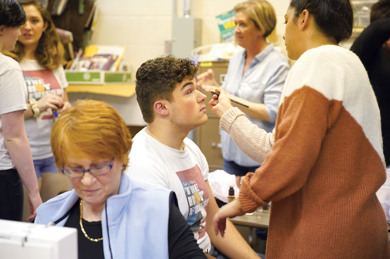"Matthew Gaston | The Sheridan press<br>Assistant director Beck Bridger applies eye make-up to Zach Allen who will performing the role of Jean-Michel in Stephanie Zukowski's production of ""Cinderella"" Tuesday, Feb. 25, 2020."